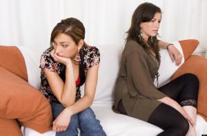 Two upset teenage girls sitting on sofa indoors at home
